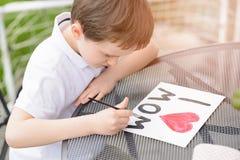 O menino da criança de 7 anos pinta o cartão para a mamã Foto de Stock
