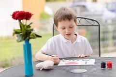 O menino da criança de 7 anos pinta o cartão para a mamã Imagens de Stock
