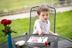 O menino da criança de 7 anos pinta o cartão para a mamã Fotos de Stock