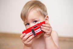O menino da criança de dois anos está jogando com um carro vermelho do brinquedo foto de stock royalty free