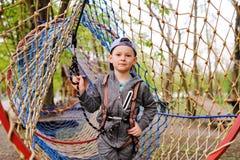 O menino da criança em idade pré-escolar da criança é um obstáculo em um curso alto da corda do equipamento do alpinism da segura imagem de stock