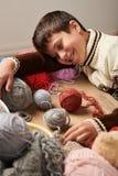 O menino da criança está aprendendo fazer malha É de sonho e de fechamento os olhos Os fios de lãs coloridos estão na tabela de m imagem de stock royalty free