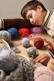 O menino da criança está aprendendo fazer malha É de sonho e de fechamento os olhos Os fios de lãs coloridos estão na tabela de m fotografia de stock