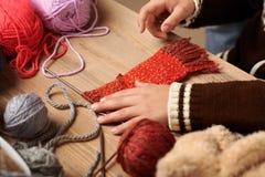 O menino da criança está aprendendo fazer malha Os fios de lãs coloridos estão na tabela de madeira Close up da mão imagens de stock royalty free