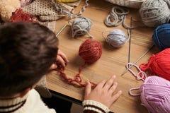 O menino da criança está aprendendo fazer malha Os fios de lãs coloridos estão na tabela de madeira São colocados como a cara de  imagens de stock