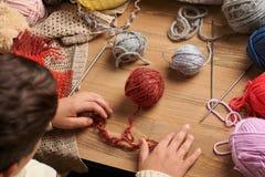 O menino da criança está aprendendo fazer malha Os fios de lãs coloridos estão na tabela de madeira São colocados como a cara de  foto de stock royalty free