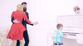 O menino da crian?a joga o piano e seus pais dan?am Jogo do piano no quarto A fam?lia da m?sica est? tendo o divertimento em casa filme