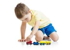 O menino da criança que joga brinquedos isolou o fundo do branco de n Imagem de Stock Royalty Free