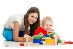 O menino da criança que joga brinquedos sere de mãe junto Imagem de Stock