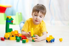 O menino da criança que joga com bloco brinca em casa Imagem de Stock