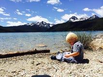 O menino da criança senta-se na borda do lago vermelho fish, saltando rochas imagens de stock royalty free