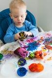 O menino da criança tira com pinturas do dedo no papel na tabela das crianças foto de stock royalty free