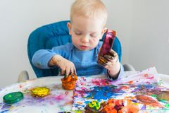 O menino da criança tira com pinturas do dedo no papel na tabela das crianças fotografia de stock royalty free