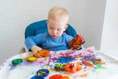 O menino da criança tira com pinturas do dedo no papel na tabela das crianças imagens de stock royalty free