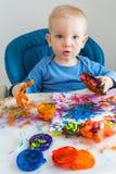 O menino da criança tira com pinturas do dedo no papel na tabela das crianças fotos de stock royalty free