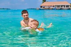 O menino da crian?a aprende nadar com pai fotos de stock royalty free