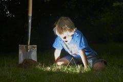 O menino da criança desenterrou um tesouro na grama Imagem de Stock
