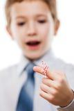 O menino da criança que olha o dedo amarrou o lembrete da memória do nó da corda Fotografia de Stock