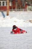 O menino da patinagem de gelo caiu para baixo na pista Foto de Stock Royalty Free