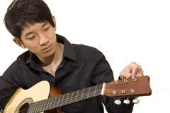 O menino de Ásia joga sua guitarra imagens de stock royalty free