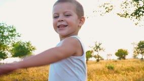 o menino de 4 anos em um t-shirt branco ri e estica para fora suas mãos Retrato de uma criança ativa alegre em uma natureza filme