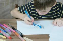 O menino de 7 anos pinta sua pintura a imagem com uma pena azul de feltro no Livro Branco Fotografia de Stock Royalty Free