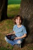 O menino de 8-9 anos senta a inclinação contra uma árvore e mantém a tabuleta disponivel fotos de stock