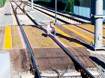 O menino de cabelo vermelho agachou-se sobre a faixa de travessia clara do trilho ao lado da plataforma do trilho da luz do metro Fotos de Stock