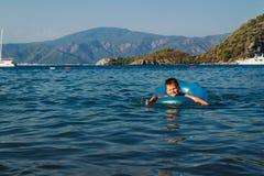 O menino de cinco anos em um boia salva-vidas azul nada no mar, Turquia fotos de stock