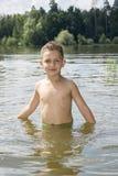O menino de dia ensolarado brilhante do verão é banhado no rio Fotografia de Stock