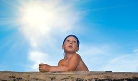 O menino de encontro ao céu azul na expectativa do som Fotografia de Stock Royalty Free