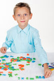 O menino de escola bonito está jogando com letras e números fotos de stock royalty free