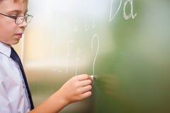 O menino de escola escreve o alfabeto inglês com giz no quadro-negro Foto de Stock Royalty Free