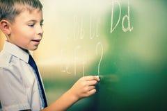 O menino de escola escreve o alfabeto inglês com giz no quadro-negro Fotos de Stock Royalty Free