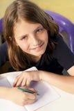 O menino de escola está escrevendo Fotos de Stock