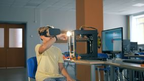 O menino de escola primária usa vidros da realidade virtual durante a classe da informática