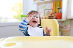 O menino de grito da criança não quer comer imagem de stock