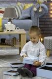 O menino de Lilttle está abrindo presentes do Natal imagem de stock royalty free
