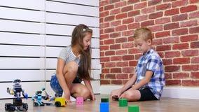 O menino de sete anos e a menina jogam robôs eletrônicos, carros, brinquedos modernos no rádio-controlo novas tecnologias no