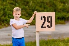 O menino de sete anos em um t-shirt branco está perto da placa com o número 29 o 29 de fevereiro nascido imagens de stock