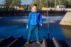 O menino de sete anos em uma jaqueta azul está perto da fonte da cidade na primavera fotografia de stock