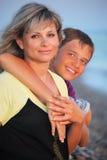 O menino de sorriso abraça a mulher nova na praia Foto de Stock
