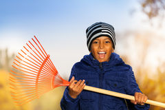 O menino de sorriso africano guarda o ancinho vermelho com emoções Fotografia de Stock
