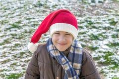 O menino de sorriso com vintage fez malha o outsi do chapéu, do lenço e do revestimento de Santa Imagens de Stock