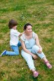 O menino de sorriso corrige o penteado da mãe no parque Foto de Stock Royalty Free