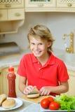 O menino de sorriso corta os bolos do Hamburger ou do sandwiche Fotos de Stock