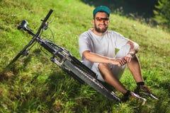 O menino de sorriso do esporte senta-se na grama perto da bicicleta exterior Fotografia de Stock Royalty Free
