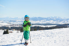 O menino de sorriso do esquiador tem o divertimento nas montanhas durante o feriado do esqui Fotografia de Stock Royalty Free