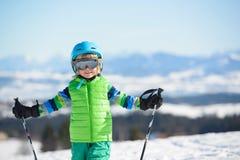 O menino de sorriso do esquiador tem o divertimento nas montanhas em um dia ensolarado Fotografia de Stock Royalty Free