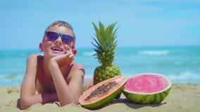 O menino de sorriso encontra-se no litoral com uma composição de frutos exóticos contra o mar vídeos de arquivo